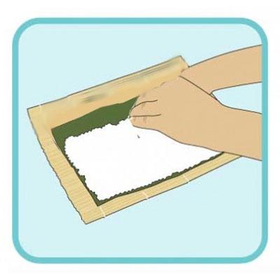 Distendere riso per sushi sull'alga nori